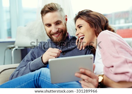 Happy couple using tablet and laughing