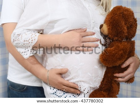 Happy couple waiting for a baby, man with his pregnant wife with a teddy bear, love concept - stock photo