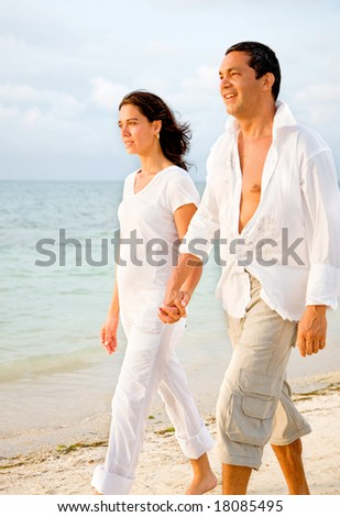 happy couple walking at the beach dressed in white