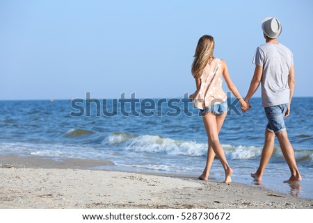 Happy couple walking back on seashore