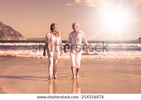 Happy couple walking barefoot on the beach on a sunny day - stock photo