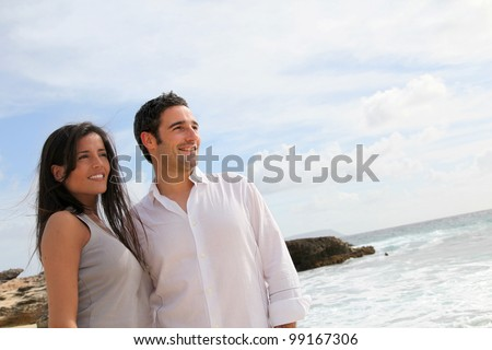 Happy couple walking by caribbean beach