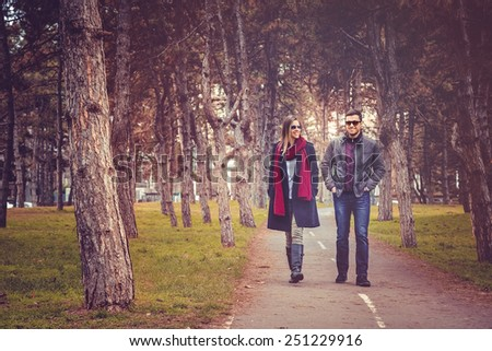 Happy couple walking in autumn city park