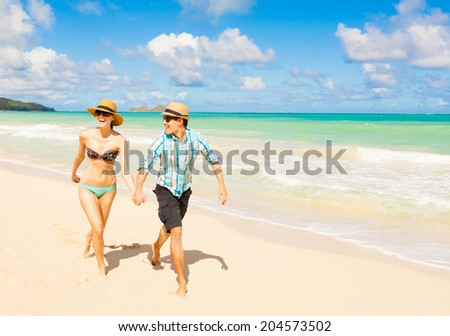 Happy couple walking on the beach.  - stock photo