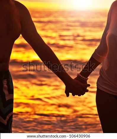Happy couple walking on the beach, holding hands, close-up on silhouette, woman and man body over sunset background, romantic honeymoon travel, family enjoying vacation, life and nature, love concept - stock photo