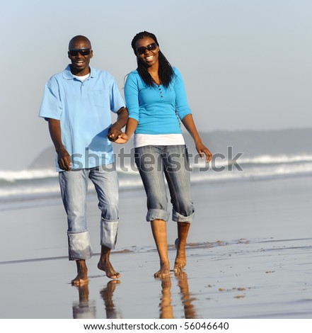 Happy couple walking on the beach in summer - stock photo