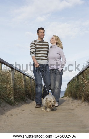 Happy couple walking with dog on boardwalk at beach - stock photo