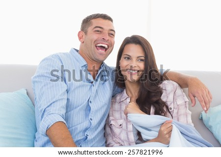 Happy couple watching TV on sofa at home - stock photo