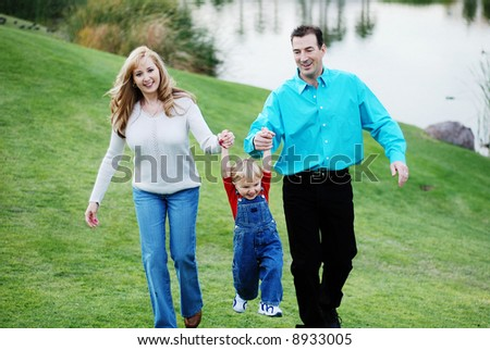 happy couple with a child smiling and enjoying their time together - stock photo