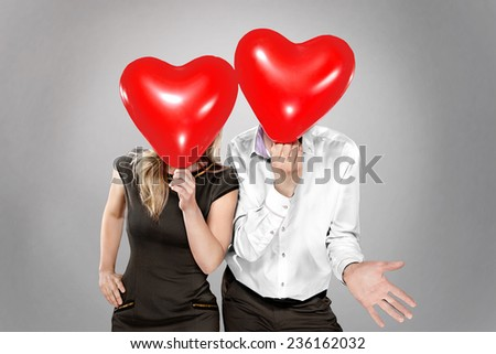 happy couple with balloons instead of a head have fund - stock photo