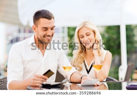 happy couple with bank card and bill at restaurant - stock photo