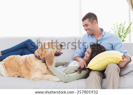 Happy couple with dog on sofa at home - stock photo
