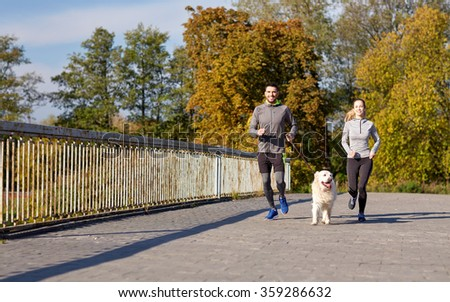 happy couple with dog running outdoors - stock photo