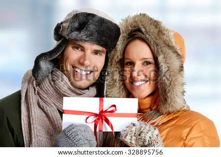 Happy couple with envelope over Christmas background.