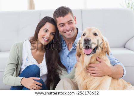 Happy couple with Golden Retriever in living room - stock photo