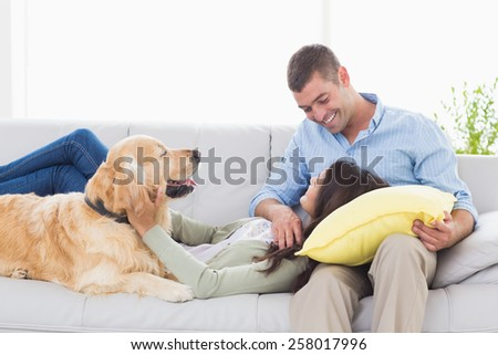 Happy couple with Golden Retriever on sofa at home - stock photo