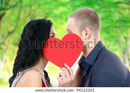 Happy couple with heart kissing outdoors - stock photo