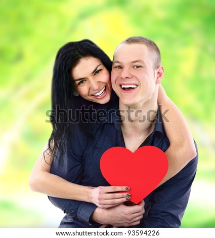 Happy couple with heart smiling outdoors - stock photo