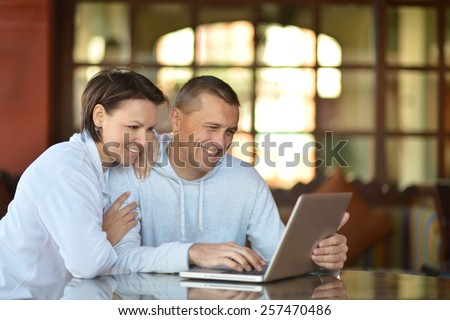 Happy couple with laptop at the table