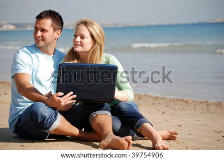 Happy couple with laptop on beach, could be traveling