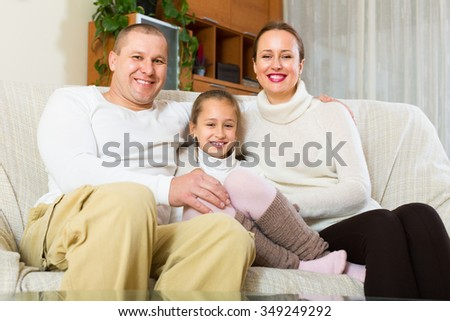 Happy couple with little daughter in home interior
