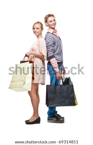Happy couple with paper bags is standing over white background