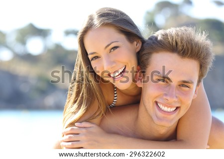 Happy couple with perfect smile and white teeth posing on the beach looking at camera - stock photo