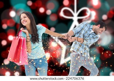 Happy couple with shopping bag against blurred christmas background - stock photo