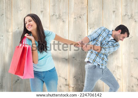 Happy couple with shopping bag against pale wooden planks - stock photo