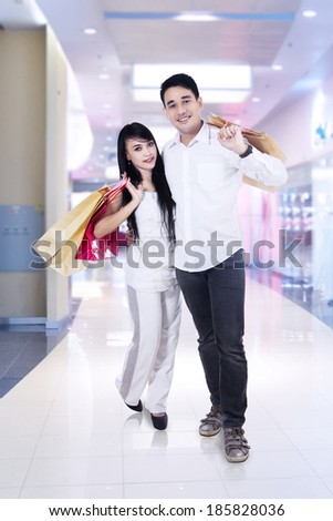 Happy couple with shopping bags in a shopping mall