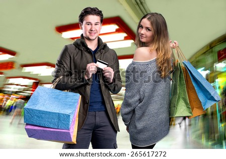 Happy couple with shopping bags in the mall. Man holding credit card