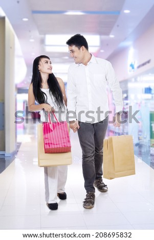 Happy couple with shopping bags in the shopping center