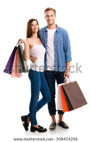 Happy couple with shopping bags, standing close to each other and looking at camera with smile. Caucasian models in love, holiday sales, shop, retail, consumer concept, isolated on white background.