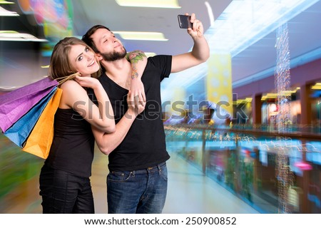 Happy couple with shopping bags taking selfie in the mall - stock photo