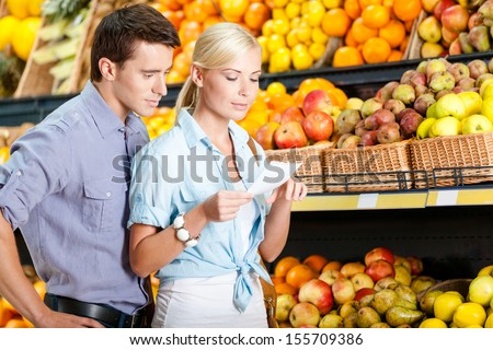 Happy couple with shopping list against the piles of fruits decides what to buy