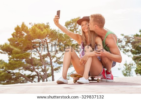 Happy couple with sitting outdoors on skateboard and taking a selfie  - stock photo