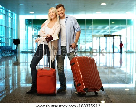 Happy couple with suitcases and map in airport - stock photo