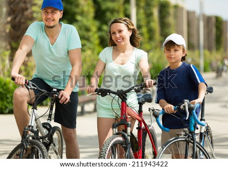 Happy couple with teenager son staying in the street  with bicycles - stock photo