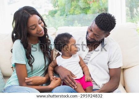 Happy couple with their baby girl on couch at home in the living room - stock photo