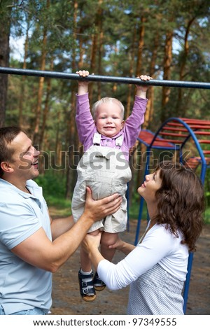 Happy couple with their little son  do exercises on the crossbar in the park