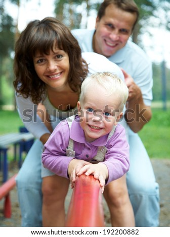 Happy couple with their little son having good time together - stock photo