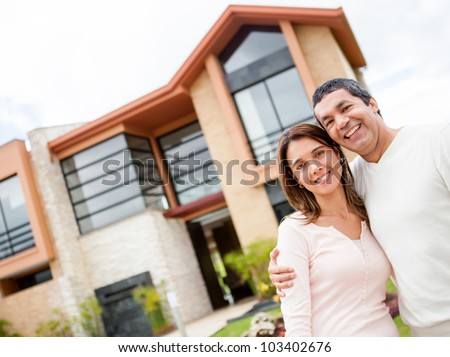 Happy couple with their new house at the background and smiling - stock photo