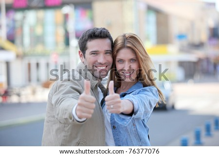 Happy couple with thumbs up in town - stock photo