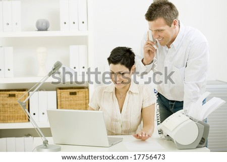 Happy couple working at home using laptop computer, smiling.