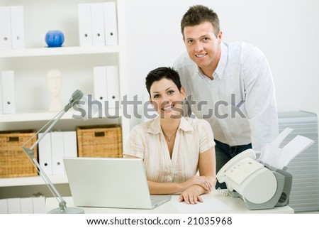 Happy couple working at home using laptop computer, smiling. - stock photo