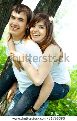 happy couple, young man giving his girlfriend piggyback ride