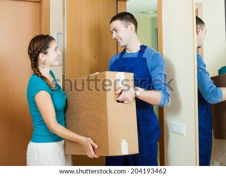 Happy courier in uniform brought package to girl at home - stock photo
