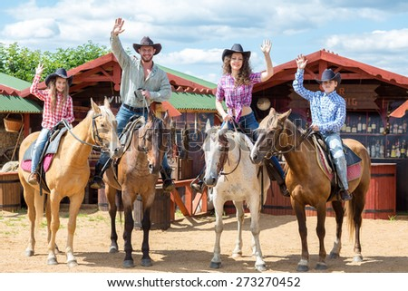 happy cowboy family of four on horsebacks waving their hands - stock photo
