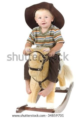 happy Cowboy toddler rides rocking horse - stock photo