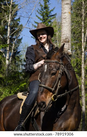Happy cowgirl in hat on brown horse - stock photo